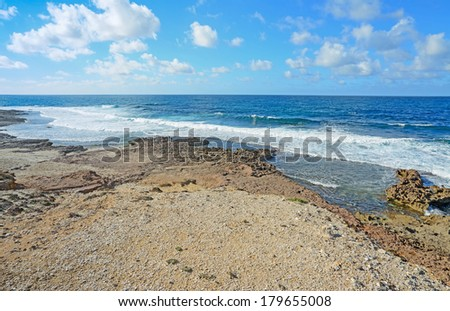 small waves and brown rocks in Argentiera, Sardinia