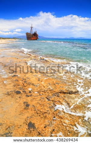 Small waves on rocky beach and rusty shipwreck in the background, Gythio, Greece