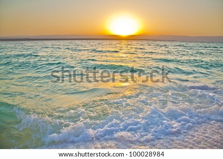 Small waves smashing against salty shores of the dead sea in Jordan - stock photo
