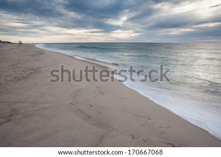 Small waves wash ashore Nauset Beach on Cape Cod, Massacusetts. This beach is a well known tourist destination and offers surfing and swimming though Great White sharks are known to be in the area. - stock photo