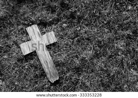 Small weathered cross on a background of grass and moss with copy space - monochrome processing - stock photo