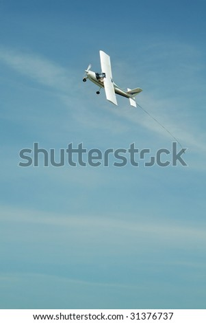 small white aeroplane flying, there's a hook on his tail which is used to carry a advertisement or so - stock photo