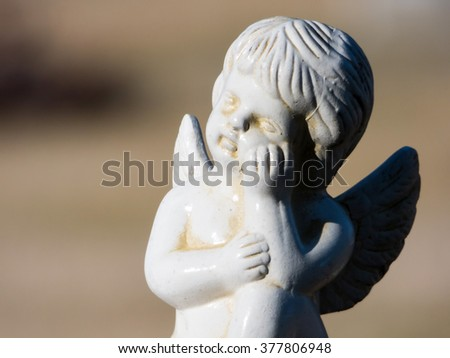 Small white angel statue in the cemetery - stock photo