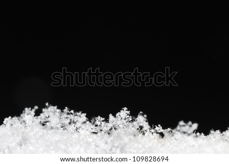 Small white background with black snow crystals lying in the winter - stock photo
