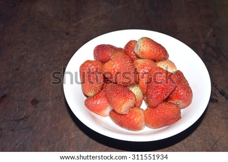 Small white bowl filled with succulent juicy fresh ripe red strawberries  - stock photo