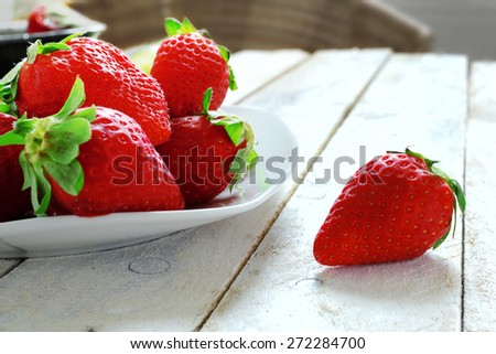 Small white bowl filled with succulent juicy fresh ripe red strawberries on an old white wooden table in a rustic kitchen - stock photo