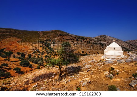 Small white church against the rough landscape of Naxos island, Greece