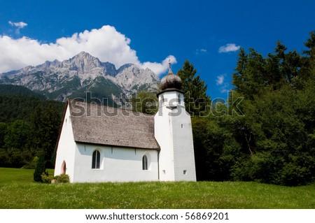 Small white church underneath the alpine peaks - stock photo