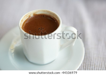 Small white cup of turkish coffee as served in a small rural cafe in Turkey. Very Shallow Depth of Field
