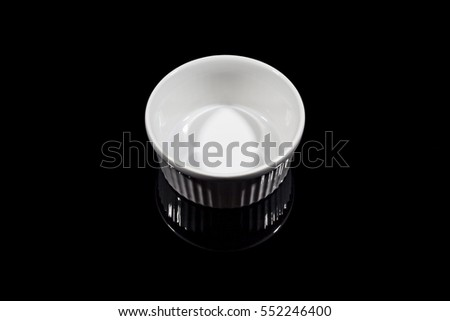 Small white deep bowl on black background from high angle with reflection