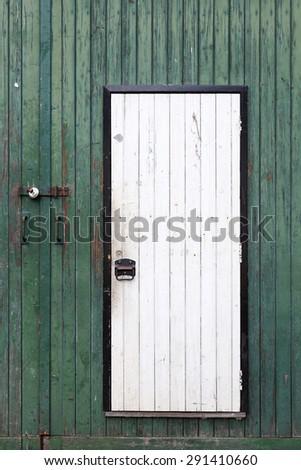 small white door in large green barn door with peeling green paint - stock photo