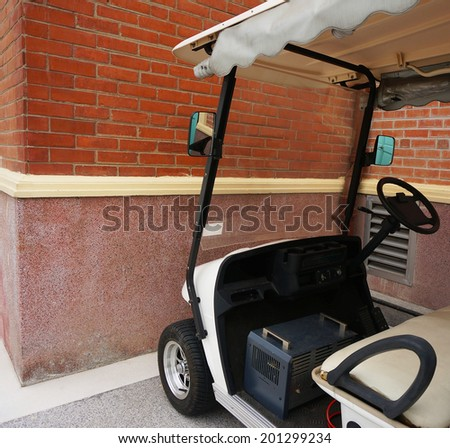 Small white golf car with a roof, parked beside a brick wall.                                - stock photo