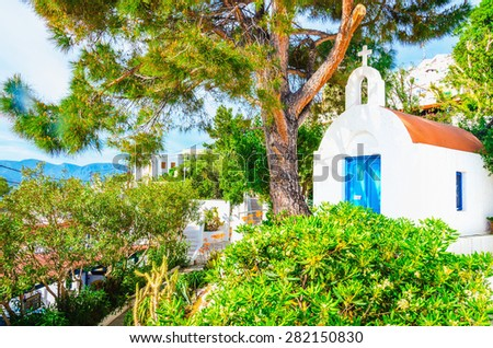Small white Greek church with blue doors typical for Greek island culture, Greece - stock photo