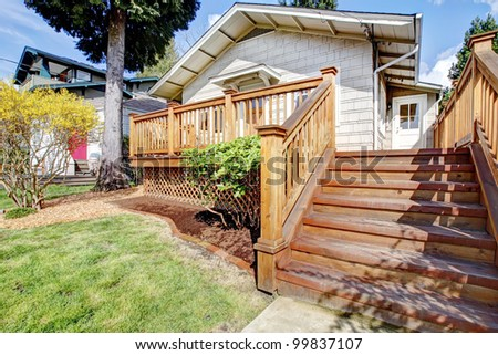 Small white house with wood deck and steps.