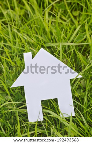 Small white paper cutout house lying on green grass, top view. - stock photo