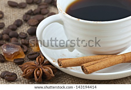 Small white porcelain cup of hot black brewed turkish coffee, caramel brown sugar crystals, cinnamon, star anise, and coffea arabica beans served on brown burlap. Coffee culture concept. - stock photo