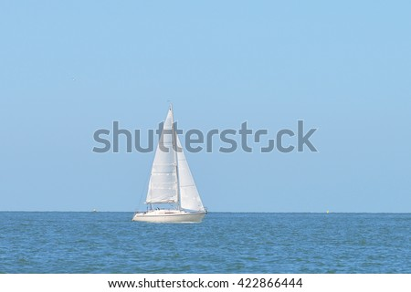Small white sail yacht sailing in blue sea