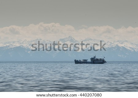 Small white ship at the Baikal lake in siberia, Russia, mountains background