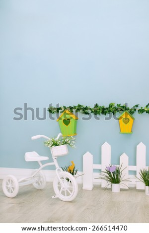 Small white tricycle with flowers, kids interior - stock photo