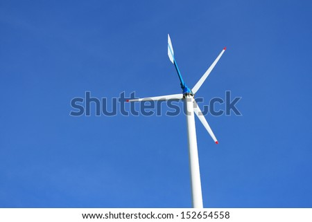 Small wind turbine on blue sky background