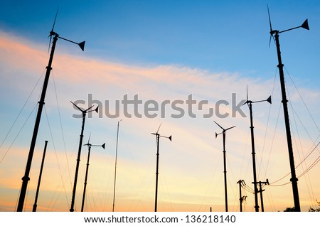small Wind turbines in the sunset, Silhouette - stock photo