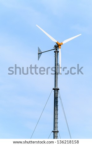 small Wind turbines on blue sky - stock photo