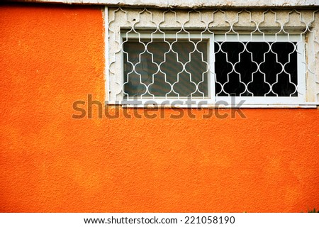 Small window with a grille and mosquito screen on the orange textured wall. Beersheba, Israel. - stock photo