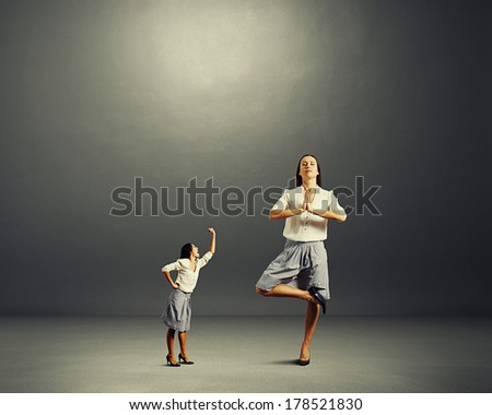 small woman screaming at big yoga woman over dark background - stock photo