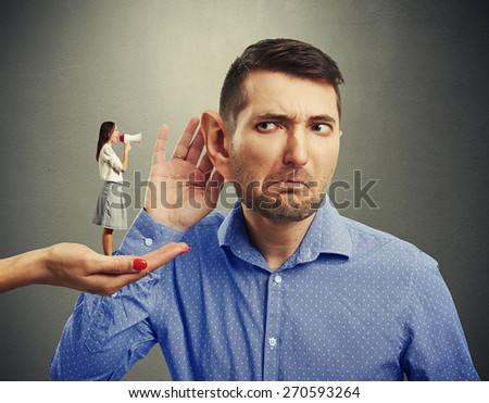 small woman standing on big female hand and screaming with megaphone at man with big ear over grey background - stock photo