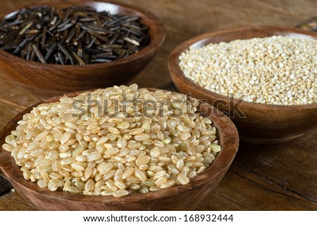 Small wood bowls filled with brown rice, quinoa and wild rice. This is shot on a wood table. - stock photo