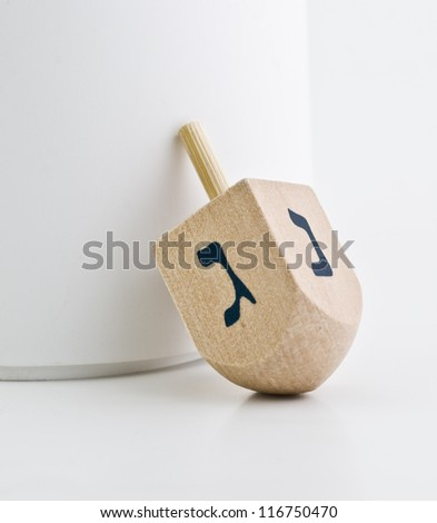 Small wood dreidel for Hanukkah on white background. - stock photo