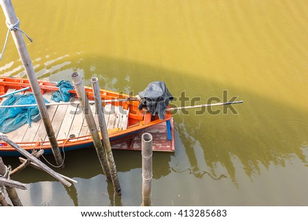 small wood fishing boat beside handmade port in the canal