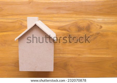 small wood house model on brown wooden background - stock photo