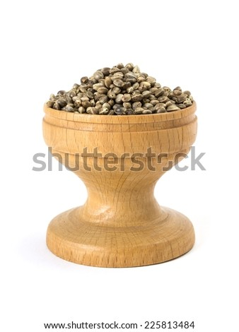 Small wooden bowl full of hemp seeds on white background - stock photo