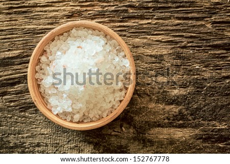 Small wooden bowl of Himalayan rock salt from the mines in Pakistan on a weathered textured wooden background, overhead view - stock photo