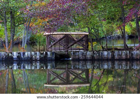 Small wooden bridge and its reflection in pond. Early Autumn, Long Island, New York. - stock photo