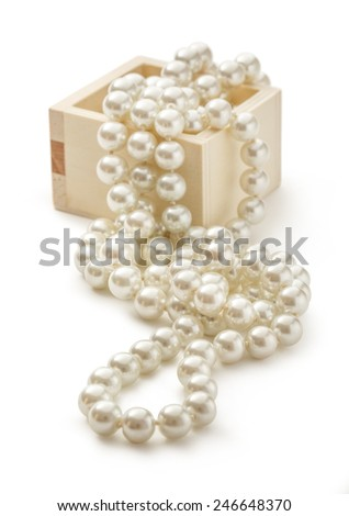 Small wooden chest with white pearl necklace - stock photo