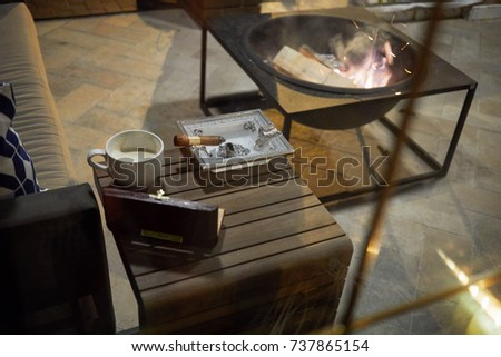 Small Wooden Cigar Table With Humidor, Ashtray With Burning Cigar, Cup Of  Coffee Near