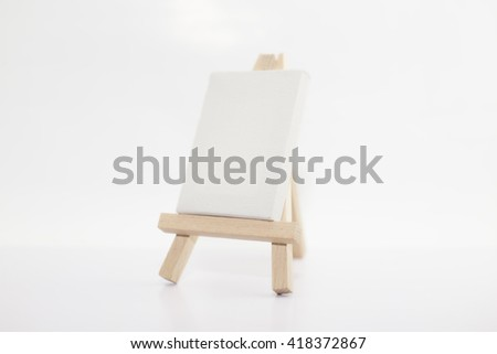 Small wooden easel and canvas for painting with blank space ready for your advertising isolated on white background.