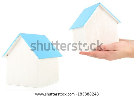 Small wooden house in hands isolated on white