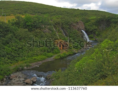 small wooden house near river and waterfall, Iceland, Skaftafell National Park - stock photo