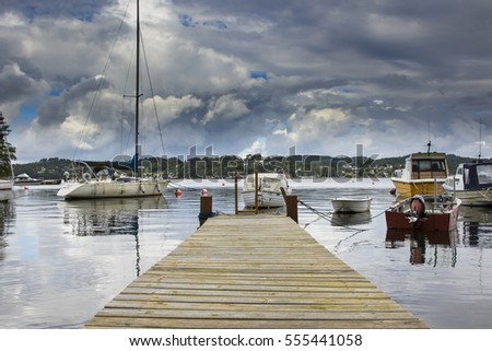 small wooden jetty and small boats in the background in Bergen Norway