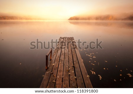 Small wooden pier on still lake in autumnal foggy morning with rising sun - stock photo
