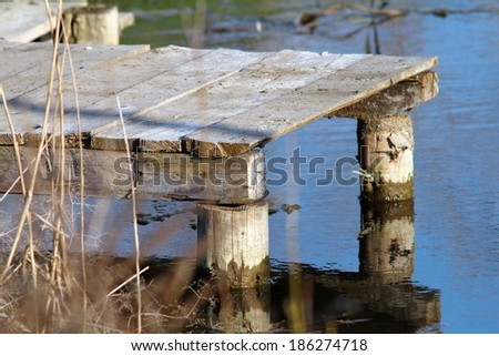 small wooden pontoon for fishing in a pond - stock photo