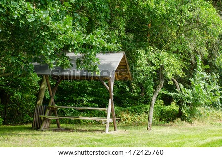 small wooden resting hut in the forest on a sunny day