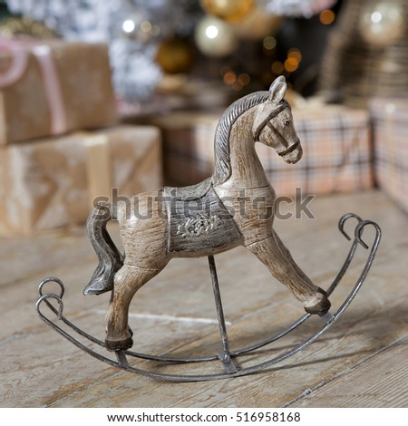 small wooden rocking horse under the Christmas tree with gifts
