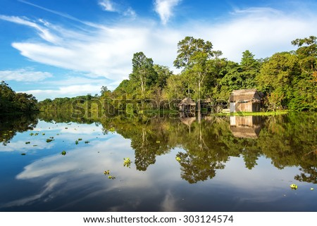 Small wooden shack in the Amazon rain forest with a beautiful reflection on the Yanayacu River near Iquitos, Peru - stock photo