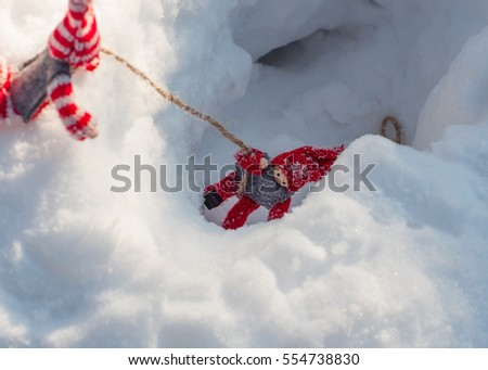 Small wooden toys in the rescue scene and assist, doll pulls a rope from a snowy ravine another doll