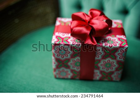 Small wrapped present with a big red satin bow on a green velvet chair.  Analog filter.  - stock photo