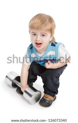 Small 2 year boy is trying to raise large metal dumbbell on white background. Young champion